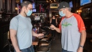 Stuart Ashton, right, co-owner of McClean's pub, scans the COVID-19 QR code of Evan Pasqualetto in Montreal, Wednesday, September 1, 2021, as the Quebec government's COVID-19 vaccine passport comes into effect. THE CANADIAN PRESS/Graham Hughes
